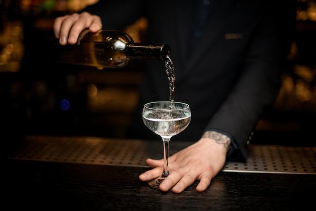 Męski barman dodaje szampana do kieliszka Premium Zdjęcia