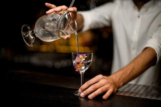 Męski Barman Nalewa Koktajl Z Miarki Z Sitkiem Do Szklanego Szkła Premium Zdjęcia