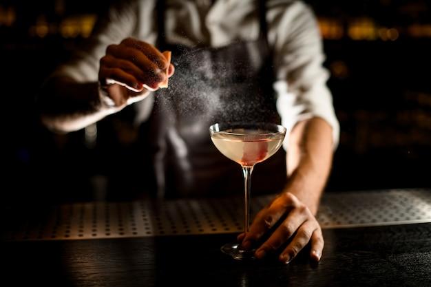 Męski Barman Serwujący Koktajl W Szklance Ozdobionej Różową Kostką Lodu Premium Zdjęcia