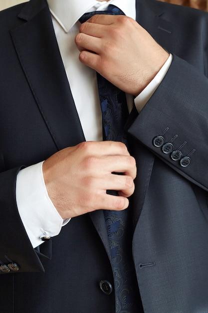 Męski biznesmen koryguje krawat. menedżer nosi Premium Zdjęcia