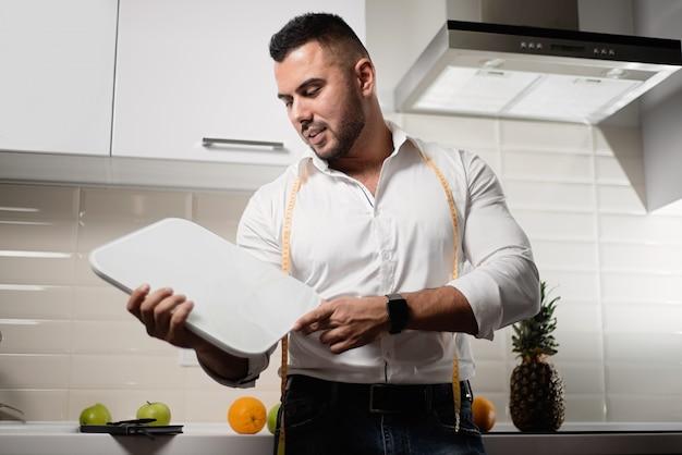Męski Dietetyka Mienie Waży W Kuchni. Premium Zdjęcia