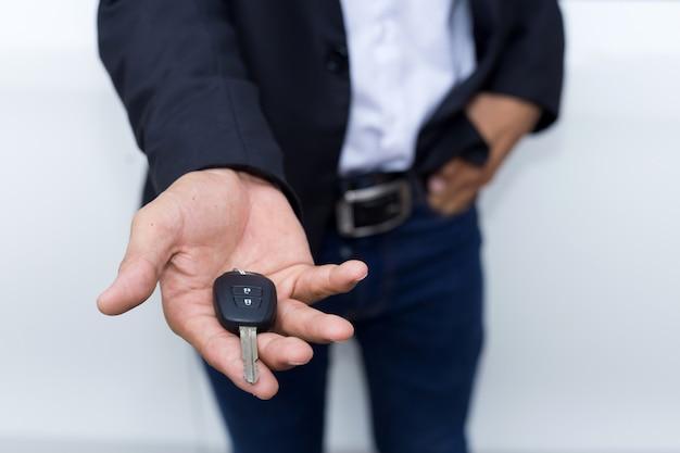 Męski dorosły biznesmen w kostiumu i trzymać samochodowego klucz w jego ręce. białe samochody w tle Premium Zdjęcia