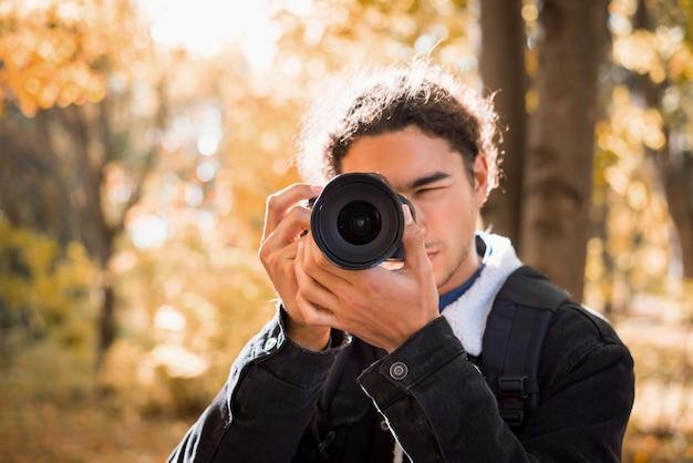 Męski fotograf z amatorską kamerą bierze obrazek natura w parku w pogodnym jesień dniu Premium Zdjęcia