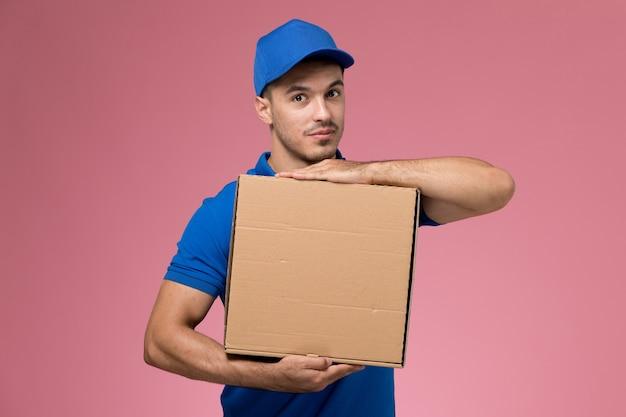 Męski Kurier W Niebieskim Mundurze, Trzymając Pudełko Dostawy żywności, Pozując Z Nim Na Różowym, Jednolite świadczenie Usług Pracownika Darmowe Zdjęcia