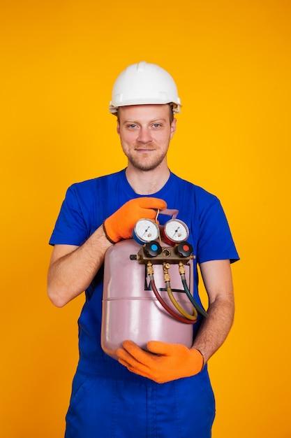 Męski Mechanik Klimatyzacji Trzyma W Rękach Cylinder Freonu, Aby Klimatyzować Klimatyzator. Premium Zdjęcia