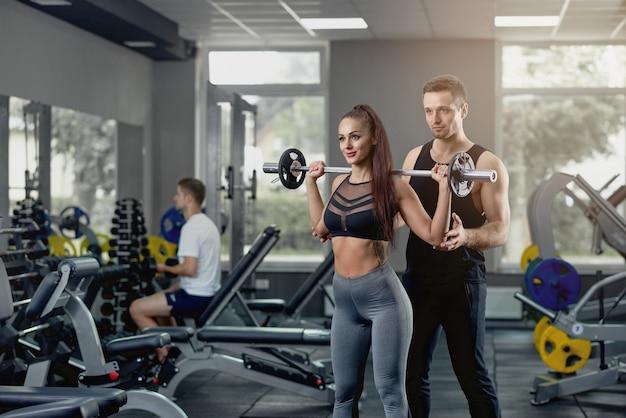 Męski Osobisty Trener Wspiera Kobiety Pracuje Z Ciężkim Barbell Przy Gym. Premium Zdjęcia
