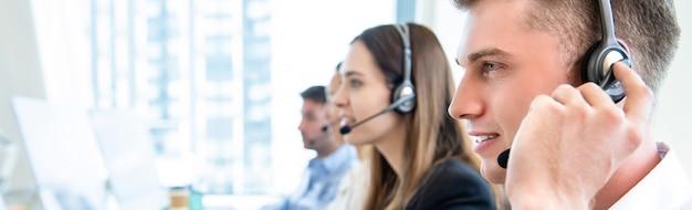 Męski Personel Operatora Z Pracującym Zespołem Telefonicznym Premium Zdjęcia