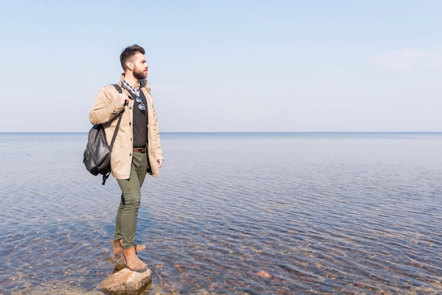 Męski podróżnik patrzeje jego idyllicznego spokojnego jezioro z jego plecakiem Darmowe Zdjęcia