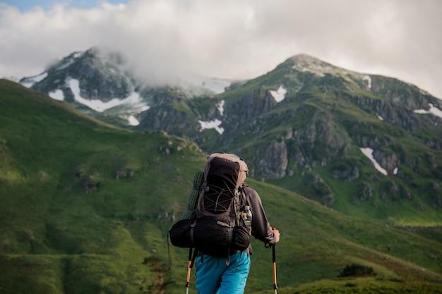 Męski turysta stoi przed górami Premium Zdjęcia