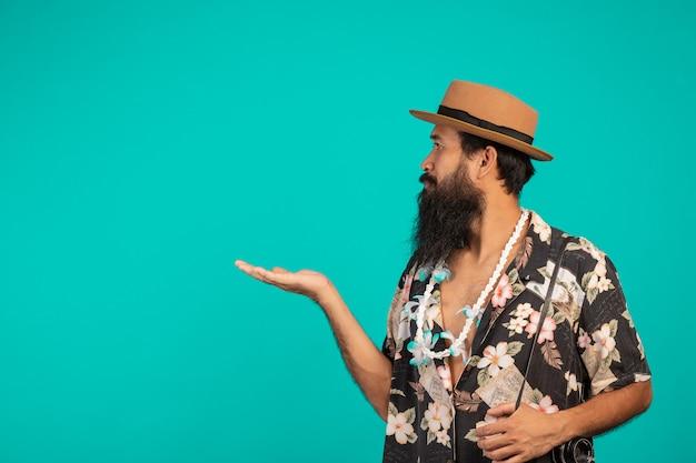 Męski turysta z długą brodą w kapeluszu i trzymający aparat na niebiesko. Darmowe Zdjęcia