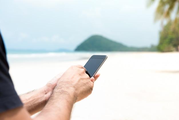 Męski turystyczny używa smartphone na wyspie przy plażą w wakacje Premium Zdjęcia