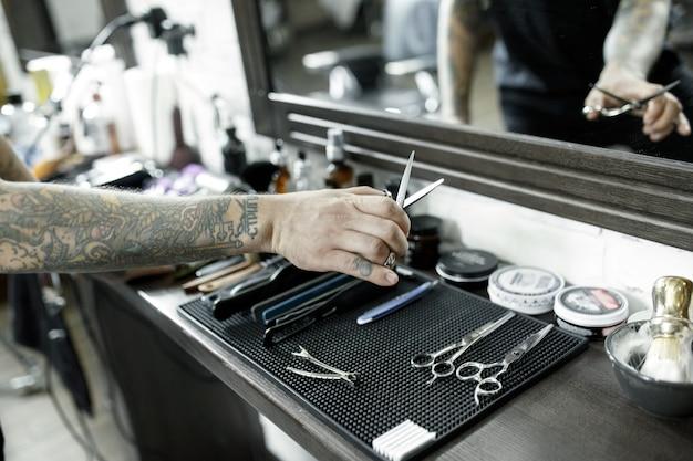 Męskie Dłonie I Narzędzia Do Strzyżenia Brody W Zakładzie Fryzjerskim. Vintage Narzędzia Fryzjera. Ręka Mistrza Ma Tatuaż Z Napisem Golenie Darmowe Zdjęcia