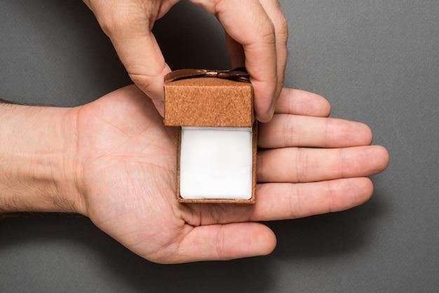 Męskie dłonie z pustym otwartym brązowym pudełkiem z biżuterią. obecny. czarny Premium Zdjęcia