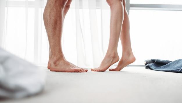 Męskie I Kobiece Nogi, Intymne Gry W Sypialni. Intymność Pary, Intymne Pragnienie Namiętnych Partnerów Premium Zdjęcia