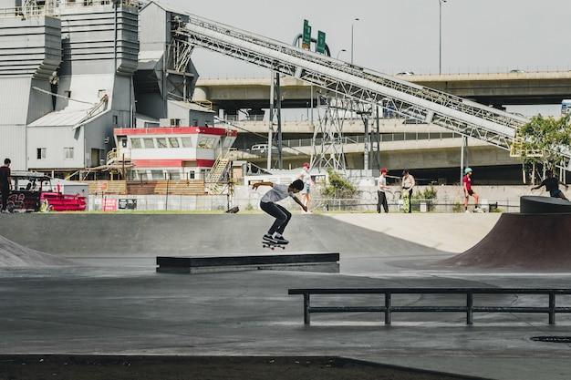 Męskie łyżwiarstwo W Skate Parku Z Budynkiem I Ludźmi Darmowe Zdjęcia