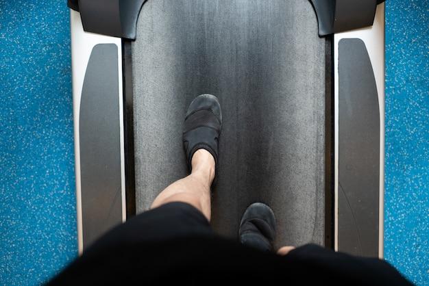 Męskie nogi chodzi i biega na karuzeli w gym. ćwiczenie treningu cardio Premium Zdjęcia