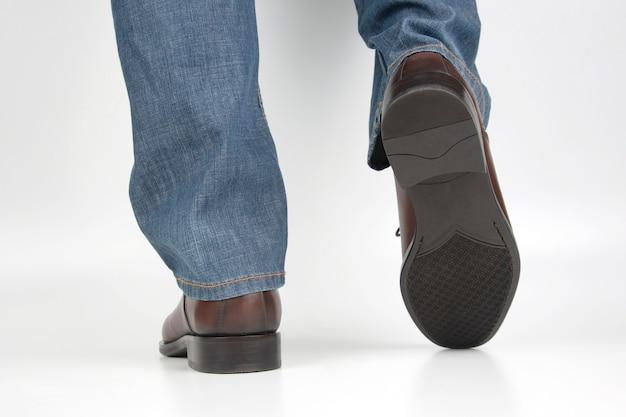 Męskie Nogi W Dżinsach I Brązowe Klasyczne Buty Na Białej Przestrzeni Premium Zdjęcia