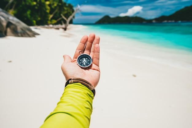 Męskiej Ręki Trzymającej Kompas Na Tropikalnej, Piaszczystej Plaży I Oceanu. Koncepcja Przygody Wakacyjnej Podróży Pov. Premium Zdjęcia