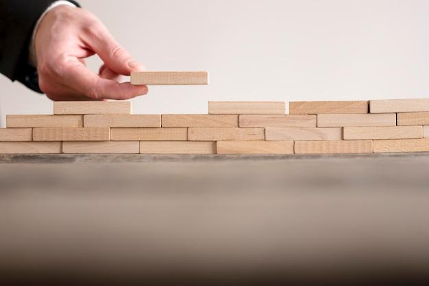 Męskiej Ręki Ukończenie Budowy ściany Z Drewnianych Cegieł Na Stole, Kopia Przestrzeń. Premium Zdjęcia