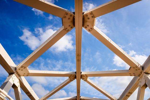 Metalowa konstrukcja belek połączonych śrubami na tle nieba. Premium Zdjęcia