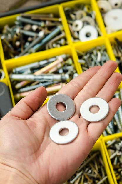 Metalowa podkładka w ręku na tle narzędzi. Premium Zdjęcia