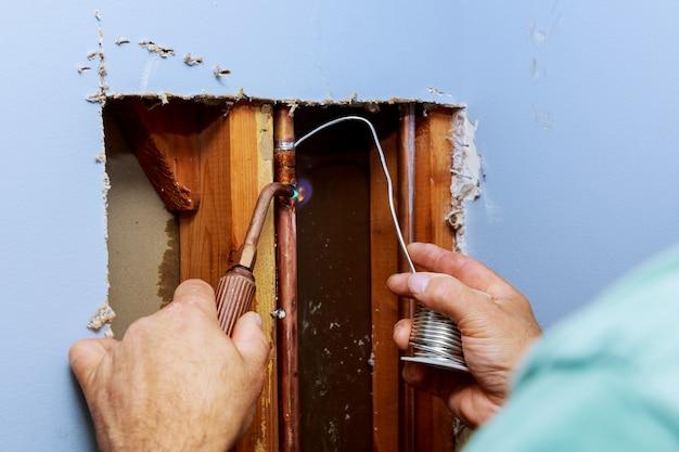 Metalowe Rury I Kształtki Domowego Systemu Wodociągowego Widziane Przez Otwór W Białej ścianie Premium Zdjęcia