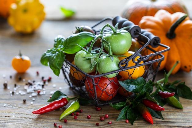 Metalowy Kosz Z Dojrzałymi Różnymi Czerwonymi, żółtymi I Zielonymi Pomidorami Na Drewnianym Stole I Liściach Bazylii Premium Zdjęcia