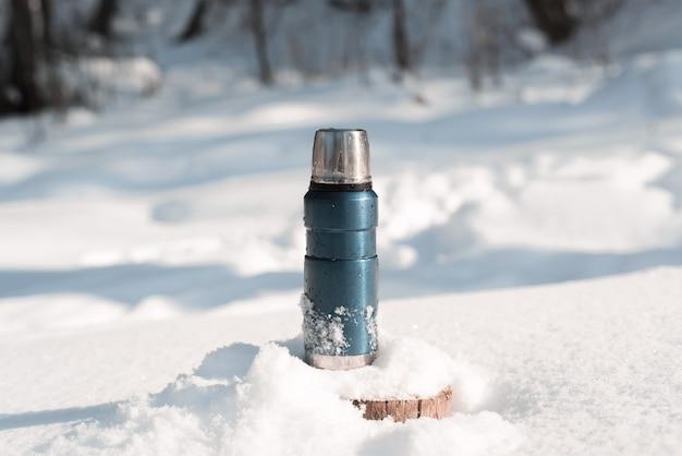 Metalowy Niebieski Termos Stojący Na Zaśnieżonym Pniu Drzewa W Zimowym Lesie W Słoneczny Dzień Premium Zdjęcia
