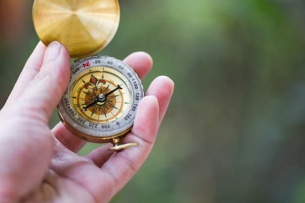 Mężczyzna Badacza Gmerania Kierunek Z Kompasem Dla Mapy - Nawigacyjna Kompasowa Podróży I Turysty Pojęcie Premium Zdjęcia
