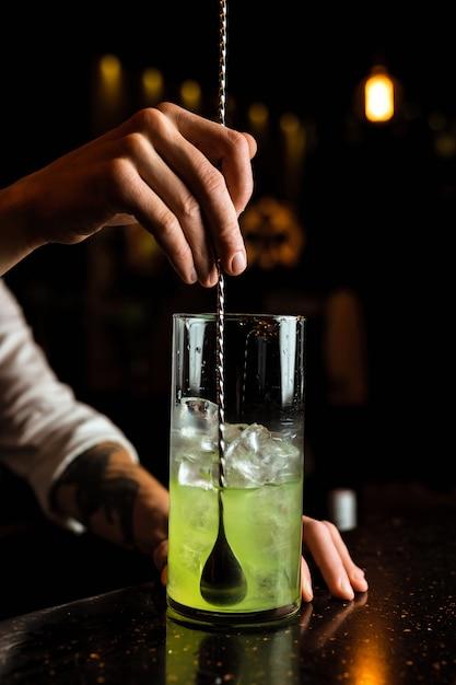 Mężczyzna Barman Przygotowuje Koktajl, Mieszając Zielony Napój W Szklance Do Mieszania Za Pomocą łyżeczki Premium Zdjęcia