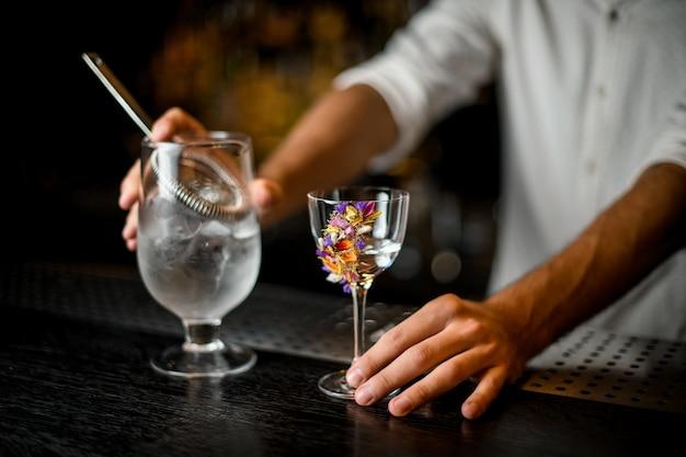 Mężczyzna Barman Trzyma Koktajl Miarka Z Sitkiem I Kwiat Zdobione Szkła Premium Zdjęcia