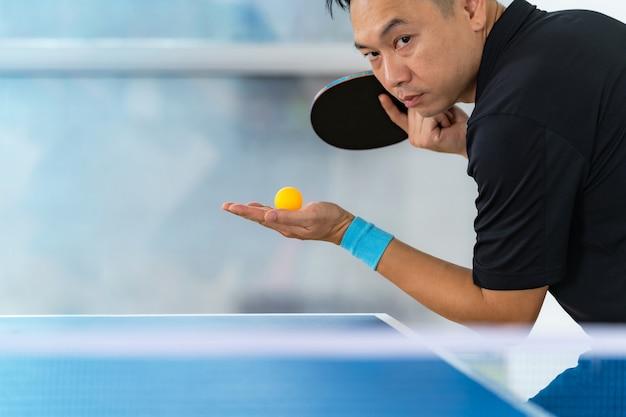 Mężczyzna bawić się stołowego tenisa z kantem i piłką w hali sportowa Premium Zdjęcia