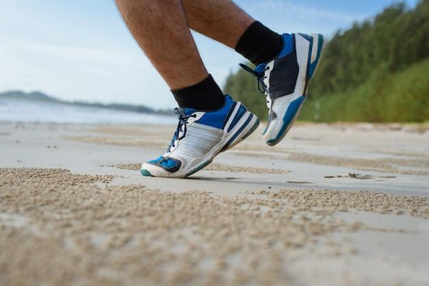 Mężczyzna biegający na plaży, zbliżenie na buty Premium Zdjęcia