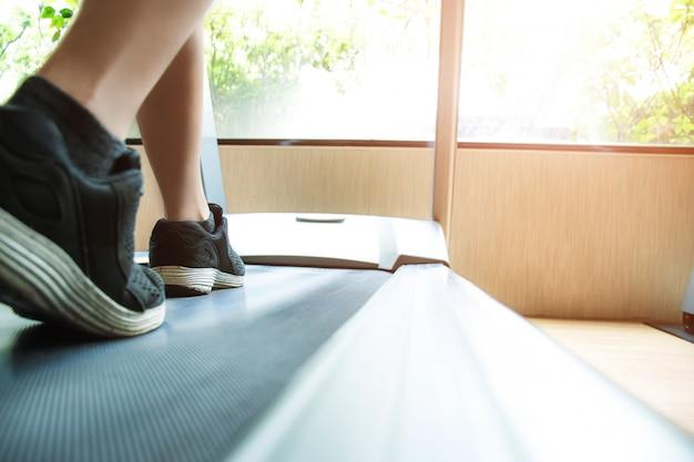 Mężczyzna biegający na siłowni na bieżni do ćwiczeń Premium Zdjęcia