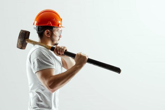 Mężczyzna budowniczy w pomarańczowym kasku z młotem saneczkowym na białym tle Premium Zdjęcia
