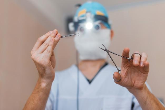 Mężczyzna Chirurg W Masce Medycznej W Okularach Z Lupami Lornetkowymi Stoi Na Sali Operacyjnej I Trzyma Nożyczki Chirurgiczne. Proces Operacyjny Premium Zdjęcia