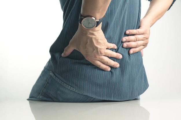 Mężczyzna cierpiący na bóle kręgosłupa, uszkodzenie kręgosłupa i problemy z mięśniami na świeżym powietrzu. Premium Zdjęcia
