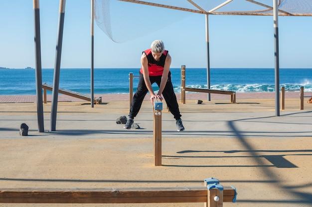 Mężczyzna ćwiczy sport w plenerowym drewnianym miastowym gym blisko morza. Premium Zdjęcia