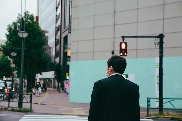 Mężczyzna Czeka Na Znak Stopu, Aby Przejść Przez Ulicę Premium Zdjęcia