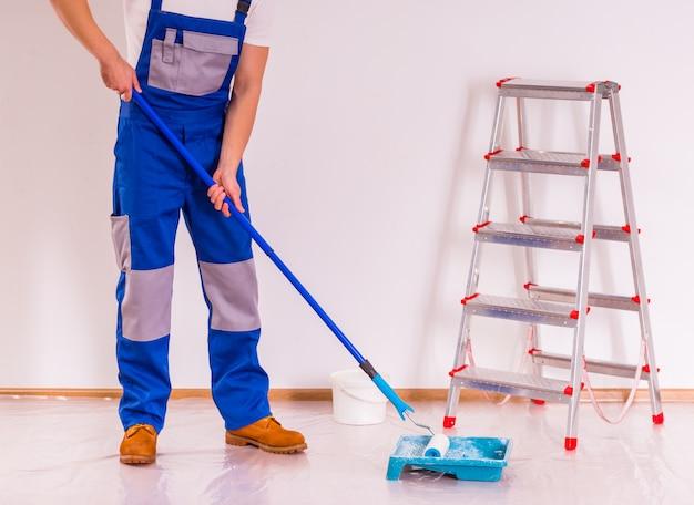 Mężczyzna czyści podłogę po naprawie. Premium Zdjęcia