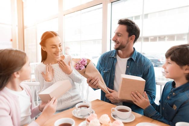 Mężczyzna Daje Kwiaty Zdziwiona Kobiety Rodziny Kawiarnia. Premium Zdjęcia