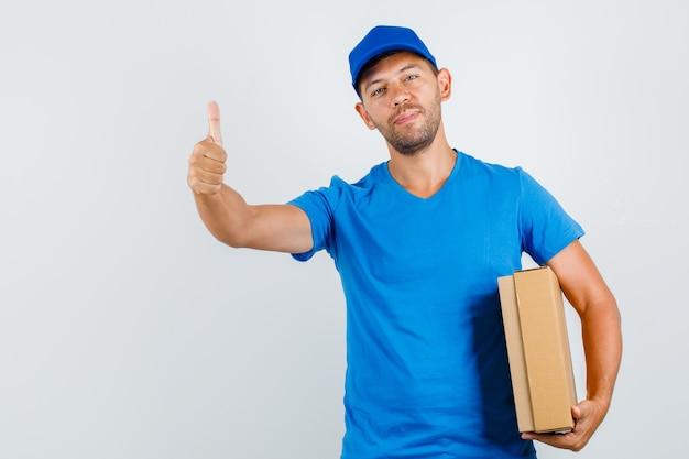 Mężczyzna Dostawy, Trzymając Karton Z Kciukiem W Niebieską Koszulkę Darmowe Zdjęcia