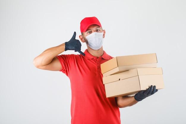 Mężczyzna Dostawy, Trzymając Kartony I Wykonujący Znak Wywoławczy W Czerwonym Mundurze, Masce Medycznej, Rękawiczkach Z Przodu. Darmowe Zdjęcia