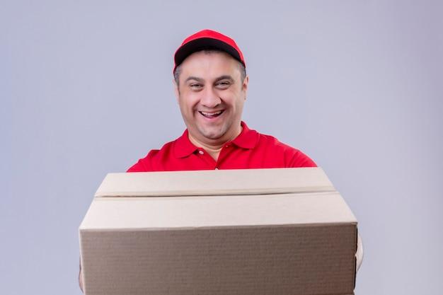 Mężczyzna Dostawy Ubrany W Czerwony Mundur I Czapkę, Trzymając Duży Karton Uśmiechnięty Przyjazny Z Szczęśliwą Twarzą Stojącą Nad Odizolowaną Białą Przestrzenią Darmowe Zdjęcia