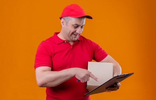 Mężczyzna Dostawy Ubrany W Czerwony Mundur I Czapkę, Trzymając Pakiet Pole I Schowek, Wskazując Palcem Wskazującym Na To Uśmiechnięty Na Pojedyncze Pomarańczowe ściany Darmowe Zdjęcia
