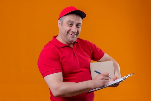 Mężczyzna Dostawy Ubrany W Czerwony Mundur I Czapkę, Trzymając Pudełko Pakiet I Schowek Z Piórem Uśmiechnięty Radośnie Nad Izolowaną Pomarańczową ścianą Darmowe Zdjęcia