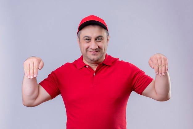 Mężczyzna Dostawy W Czerwonym Mundurze I Czapce Gestykuluje Ręką Uśmiechniętą Stojącą Koncepcję Języka Ciała Darmowe Zdjęcia