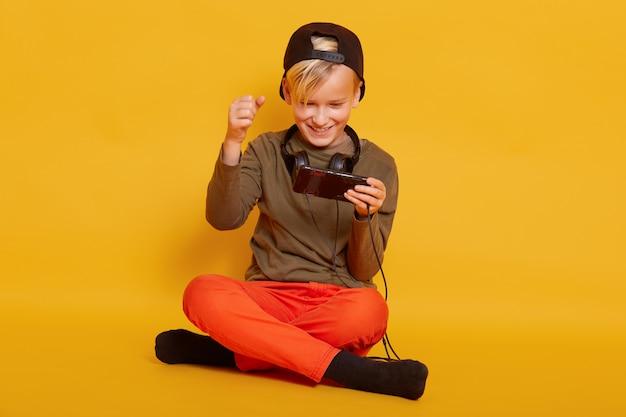 Mężczyzna Dziecko Grający W Grę Na Telefon Komórkowy, Siedząc Na Podłodze W Kolorze żółtym, Grając W Swoją Ulubioną Grę Online Przez Telefon, Trzyma Skrzyżowane Nogi, Zaciska Pięści. Darmowe Zdjęcia