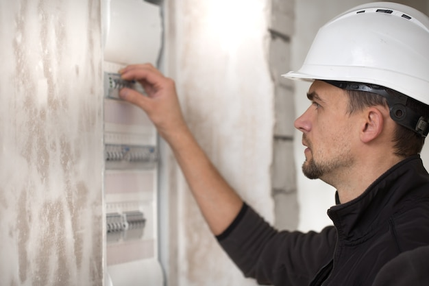 Mężczyzna, Elektryk Pracujący W Tablicy Rozdzielczej Z Bezpiecznikami. Instalacja I Podłączenie Sprzętu Elektrycznego. Darmowe Zdjęcia