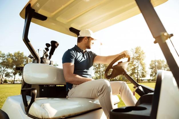 Mężczyzna Golfista Jazdy Wózkiem Z Torbą Kijów Golfowych Darmowe Zdjęcia